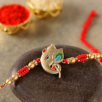 Alluring Rose Gold Ganesha Rakhi:Rakhi With Sweets to China