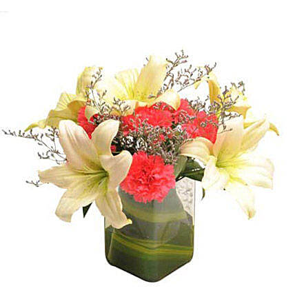 Glass vase arrangement of 6 dark pink carnations, 2 white asiatic lilies, seasonal filler and draceane leaves:Lilies for Birthday