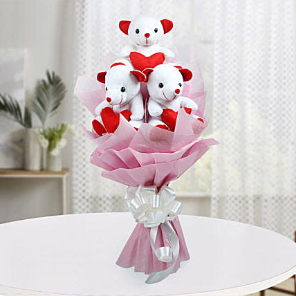 A bouquet of three red and white teddy bears wrapped with pink paper packaging and white ribbon:Soft Toys