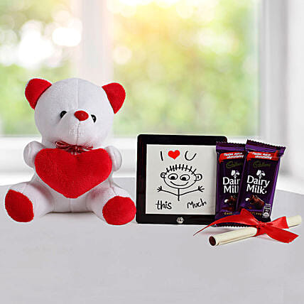 A hamper containing table top, dairy milk , cream teddy bear and a love message gifts