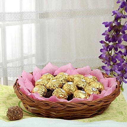 Ferrero rocher chocolates and artificial pink paper petals in a round cane basket:Send Gift Baskets