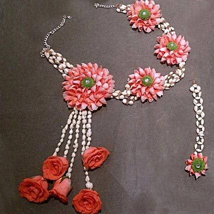 A set of floral necklace and mang tikka with orange roses, green daisy, and mogra