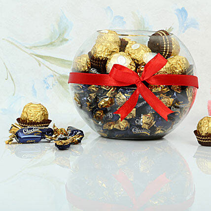 Ferrero rocher and cadbury chocolairs gold candies in a glass vase wrapped with red ribbon:Candies