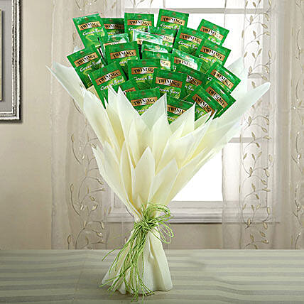 A bouquet containing twinings of london green tea wrapped with white paper and green raffia
