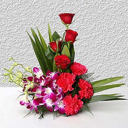 Cane basket arrangement of 4 purple orchids, 4 dark pink carnations, 4 red roses and arica palm leaves flowers:Flower Basket Arrangements