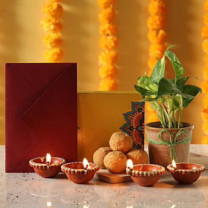 money plant n greeting with sweet for diwali