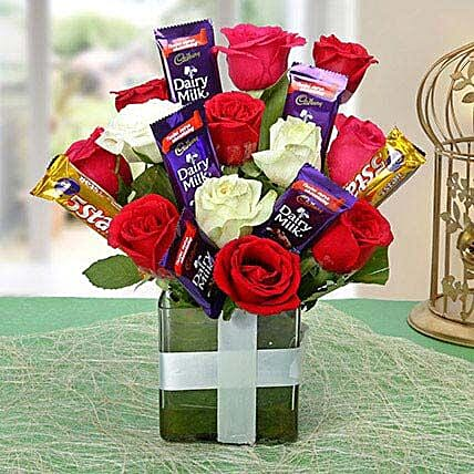 Glass vase arrangement of roses and chocolates