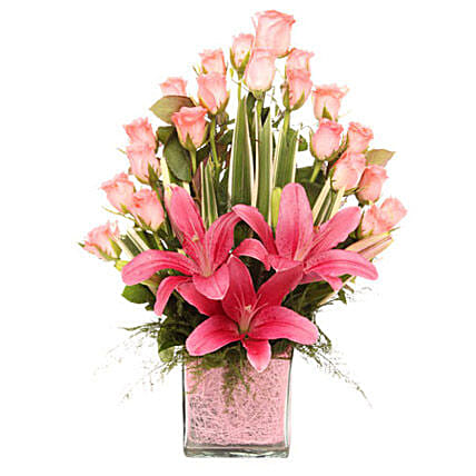 Glass vase arrangement of 20 pink roses, 3 pink asiatic lilies, draceane leaves, and vase filler gifts