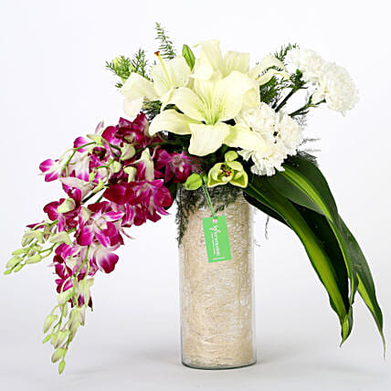 Glass vase arrangement of 6 purple orchids, 3 white asiatic lilies, 6 white carnations with draceane leaves and vase filler flowers gifts:Send Anniversary Gifts to Chennai