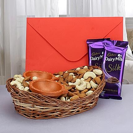 Dry fruits with diyas, greeting card and chocolates