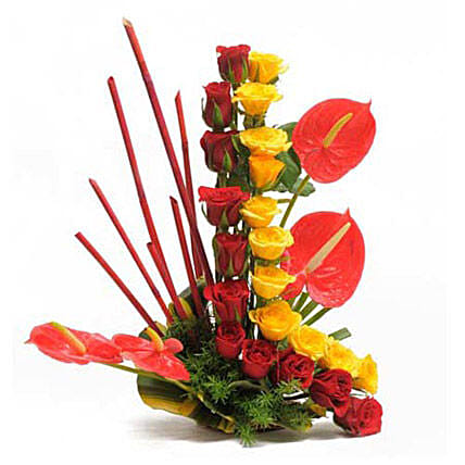 Modern Basket - Basket arrangement of 22 Red and yellow roses with 4 red Anthuriums.
