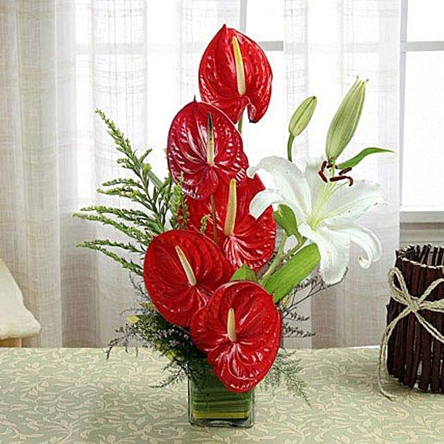 Square glass vase arrangement of flowers:Anthuriums
