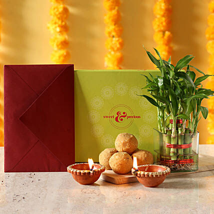 Lucky bamboo with greeting card, sweets and diyas