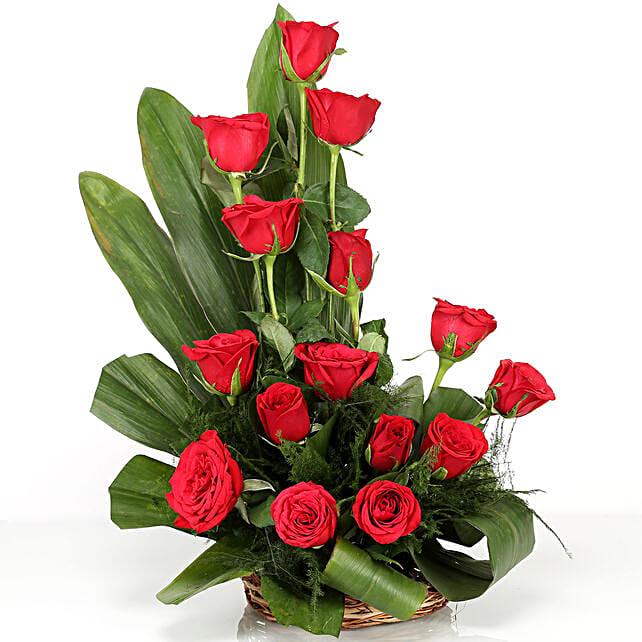 Cane basket arrangement of 15 red roses, draceane leaves and seasonal filler flowers gifts