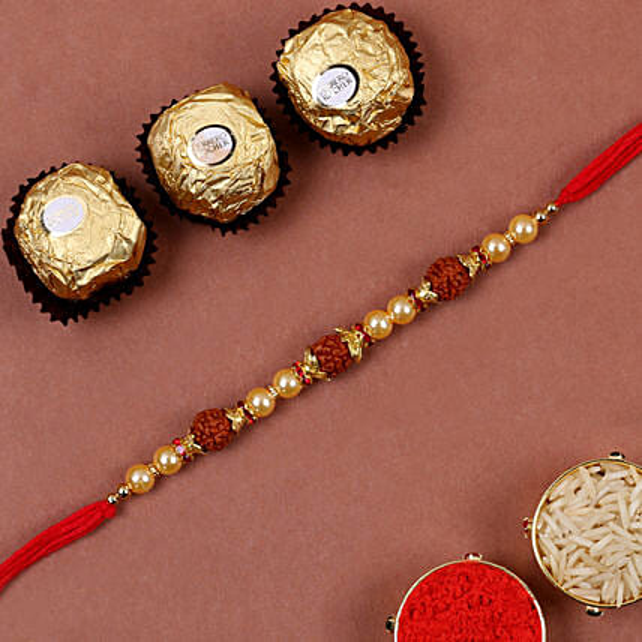 Golden Red Rudraksh Rakhi And 3 Pcs Ferrero Rocher:Rakhi with Greeting Cards to Singapore