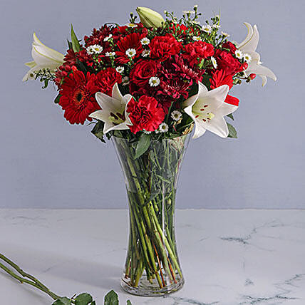 Mix Of Red Flowers In A Glass Vase