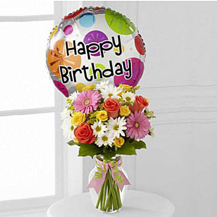 Coral roses, yellow spray roses, hot pink gerbera's, white daisies, solidago and greens in a classic clear glass vase tied with pink satin and green chenille ribbons...AND a Happy Birthday Mylar Birthday